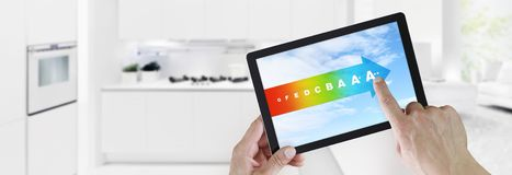 Energy efficiency concept hand touch digital tablet with colored symbols on blue sky, isolated on blurred kitchen background web. Energy efficiency concept hand royalty free stock image