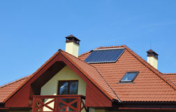 Energy efficiency concept. Solar water panel heating on new house roof Stock Photography