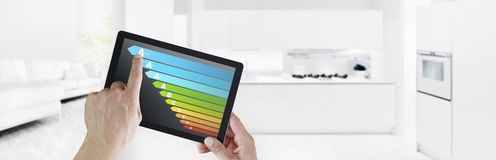Energy efficiency hand touch digital tablet screen with colored symbols on interior kitchen background web banner and copy space. Energy efficiency hand digital stock image