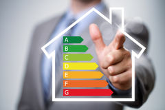 Energy efficiency in the home. Businessman pointing to energy efficiency rating chart and house icon concept for performance, efficiency and environmental Stock Images