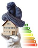 Energy efficiency label for house / heating and money savings - model of a house with cap in a hand in gloves. On white background Stock Photos
