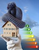 Energy efficiency label for house / heating and money savings - model of a house with cap in a hand in gloves. Against the sky Royalty Free Stock Photos