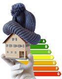 Energy efficiency label for house / heating and money savings - model of a house with cap in a hand in gloves. Against white background royalty free stock photo