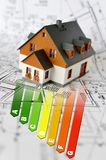 Energy efficiency label for house / heating and money savings - model of a house. On the blue prints stock photo