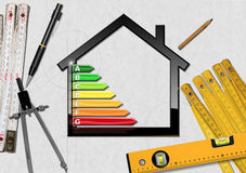 Energy Efficiency - Project of Ecological House. House with energy efficiency rating 3D illustration on a desk with folding rulers, pencils and a drawing compass Royalty Free Stock Photo