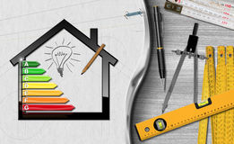 Energy Efficiency - Project of Ecological House. House with energy efficiency rating 3D illustration on a desk with folding rulers, pencils and a drawing compass Royalty Free Stock Photography