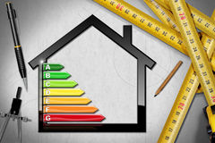 Energy Efficiency - Project of Ecological House. House with energy efficiency rating 3D illustration on a desk with tape measures, pencils and a drawing compass Stock Image