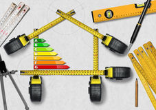 Energy Efficiency - Project of Ecological House. Energy Efficiency - Tape measures in the shape of house with energy efficiency rating. Project of ecological Stock Photos