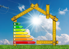 Energy Efficiency - Project of Ecological House. Wooden folding ruler in the shape of house with energy efficiency rating. Concept of ecological house project royalty free stock image