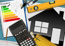 Energy Efficiency Rating with Calculator and House. Energy efficiency rating graph in a notebook on a desk with a model house, calculator, wooden folding ruler Royalty Free Stock Image