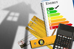 Energy Efficiency Rating with Calculator and House. Energy efficiency rating graph in a notebook with a shadows of a house, calculator, wooden folding rulers Royalty Free Stock Photo