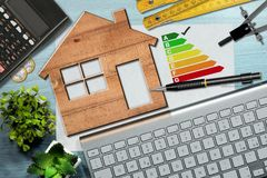 Energy Efficiency Rating - Wooden House Model. Energy efficiency rating graph on a desk with a wooden house model, calculator, folding ruler, drawing compass Royalty Free Stock Photos