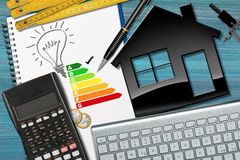 Energy Efficiency Rating with House Model. Energy efficiency rating graph in a notebook on a desk with a model house, calculator, light bulb, drawing compass Stock Image