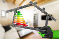 Energy Efficiency - Ruler in the Shape of House. Energy Efficiency - Hand with work glove holding a metal ruler in the shape of house with energy efficiency Royalty Free Stock Image