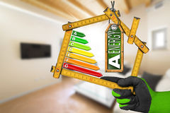 Energy Efficiency A - Ruler in the Shape of House. Energy Efficiency A - Hand with work glove holding a wooden folding ruler in the shape of house with energy Stock Image