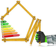 Energy Efficiency - Ruler in the Shape of House. Energy Efficiency - Hand with work glove holding a wooden folding ruler in the shape of house with energy Royalty Free Stock Images