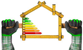 Energy Efficiency - Ruler in the Shape of House. Energy Efficiency - Hands with work gloves holding a wooden folding ruler in the shape of house with energy stock photo