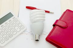 Energy efficiency and saving concept. Light bulb,calculator,penc. Il,notebook and graph on the wooden table stock image