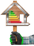 Energy Efficiency - Sign in the Shape of House. Hand with work glove holding a wooden sign in the shape of house with energy efficiency rating. Isolated on white Stock Image
