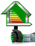 Energy Efficiency - Sign in the Shape of House. Hand with work glove photo holding a green sign in the shape of a house 3d illustration with energy efficiency Royalty Free Stock Photography