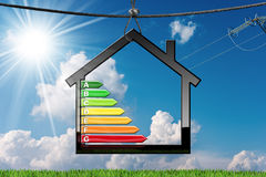 Energy Efficiency - Symbol with House Model. Energy Efficiency - House Model with energy efficiency rating 3D illustration hanging on a steel cable on a blue sky Royalty Free Stock Images
