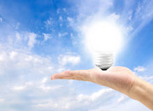 Energy efficient bulb in hand with blue sky in background Stock Images