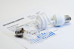 Energy efficient house. Energy efficient and broken incandescent bulbs on electric bill royalty free stock photos