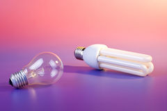 Energy-efficient lamp versus usual lamp. On color background royalty free stock photography