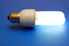 Energy efficient light bulb. Energy efficient lit light bulb on blue background Royalty Free Stock Photos