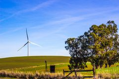 Energy Efficient Wind Mill In Open Field. With Blue Sky Background Stock Photos