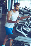 Energy and effort. Side view of young handsome man in sportswear looking away while working out on stepper at gym Royalty Free Stock Photography