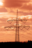 Energy in Fire Sky. A single power pole silhouette with orange sunset sky Royalty Free Stock Photo
