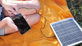 Energy-generating technology, close up, hands girl connects from solar panel to mobile phone outside. Young woman charge cell phone from solar charger, modern stock video