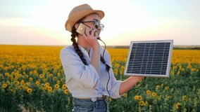 Energy generation, woman talk phone and keep solar battery tracking sun to charge battery, girl speaks by mobile phone. And holds solar panel in background stock footage