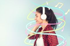 Energy girl with white headphones listening to music with closed eyes on blue background in studio. Energy girl with white headphones listening to music with stock image