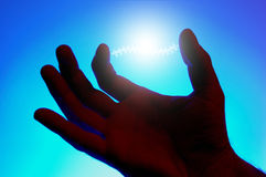 Energy glowing between fingers Stock Photo