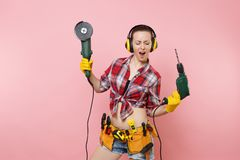 Energy handyman woman in gloves, noise insulated headphones, kit tools belt full of instruments holding power saw. Electric drill isolated on pink background royalty free stock image