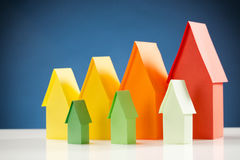 Energy Label Houses with Blue Background. Two rows of miniature paper houses in energy label colors with a blue background stock photo