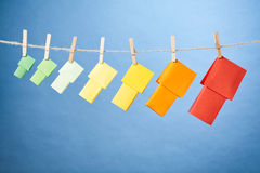 Energy Label Houses on a Rope Line. Seven paper houses in the colors of the European energy label standard hanging from a rope line by clothespins on a light royalty free stock photo
