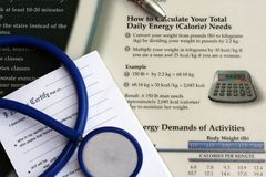 Daily energy needs. Doctors' desk with body mass index chart on it, also showing doctors' stethoscope, pen and prescription pad royalty free stock photo