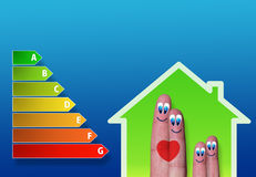 Low-power of green house with cute fingers family. Energy performance scale with green house and cute fingers family Stock Images