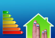 Low-power house and energy chart and cute fingers inside. Energy performance scale with low-power house and cute finger family inside Royalty Free Stock Photography