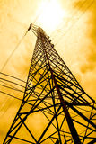 Energy power concept: high voltage pylons with cloud and sun bac Stock Photography