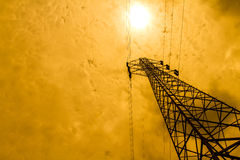 Energy power concept: high voltage pylons with cloud and sun bac Stock Images