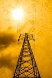 Energy power concept: high voltage pylons with cloud and sun bac Royalty Free Stock Images