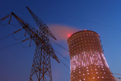 Energy production. A beautifully lit cooling tower and power line at dusk Stock Photo