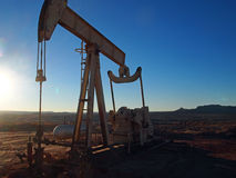 Energy Production. Pumping hydrocarbons at a desert well on a winter afternoon Royalty Free Stock Photo