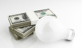 Energy saver light bulb with dollars Royalty Free Stock Photography