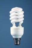 Energy Saving Bulb. An image of a white energy saving bulb against a medium blue background Stock Photos