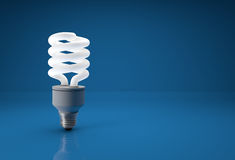 Energy saving bulb on blue background with place for text. royalty free stock photo